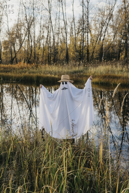 Person dressed up as a ghost stands near a lake