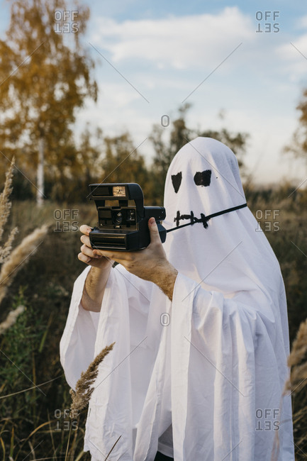 Person dressed up as a ghost taking pictures on an instant camera outside