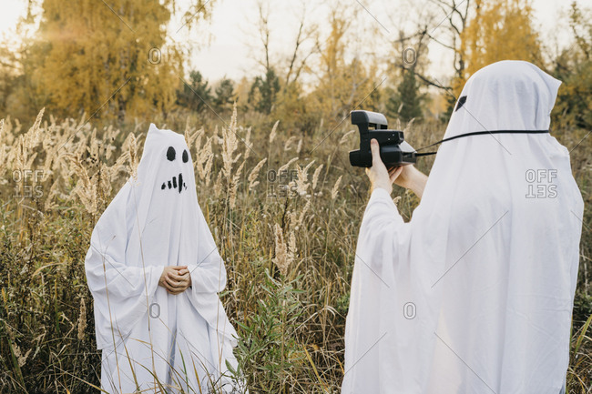 Two people dressed up as ghosts taking portraits