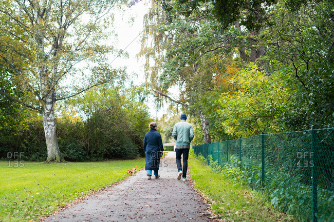 Two people walking with their dog on footpath in park