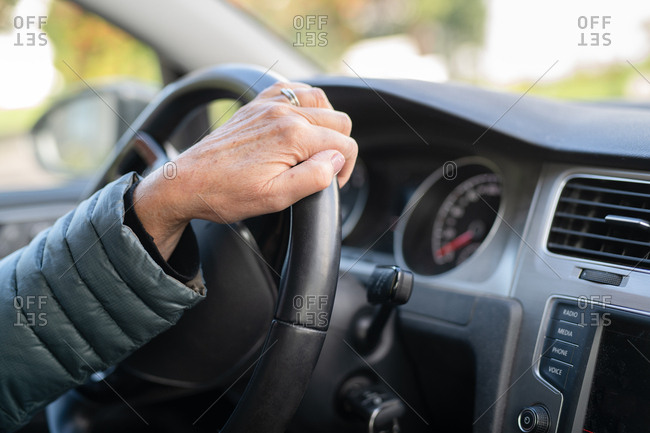 Person's hand on steering wheel of car