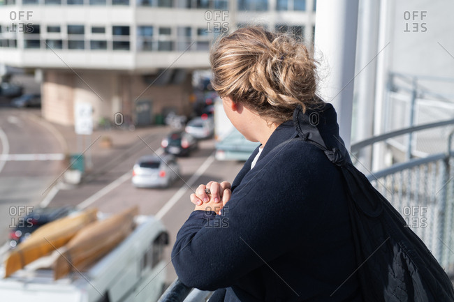 Woman standing on balcony looking at city street