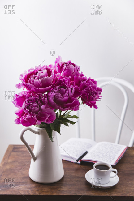 Pink peonies in a pitcher with a journal on a wooden table