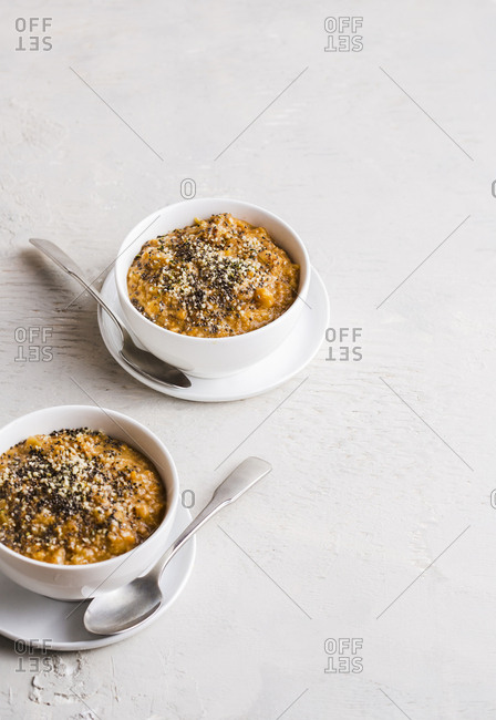 Two bowls of pumpkin spice oatmeal with negative space