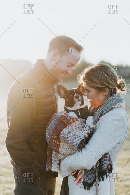 Couple carrying their puppy in woollen blanket