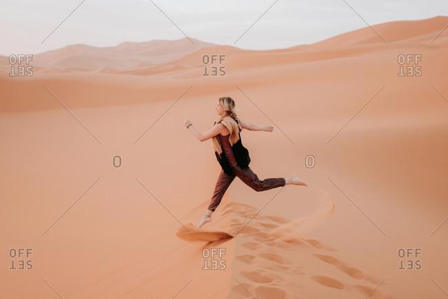 Woman running in desert, Douba, Morocco