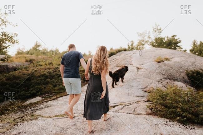 Couple walking with pet dog, Algonquin Park, Canada