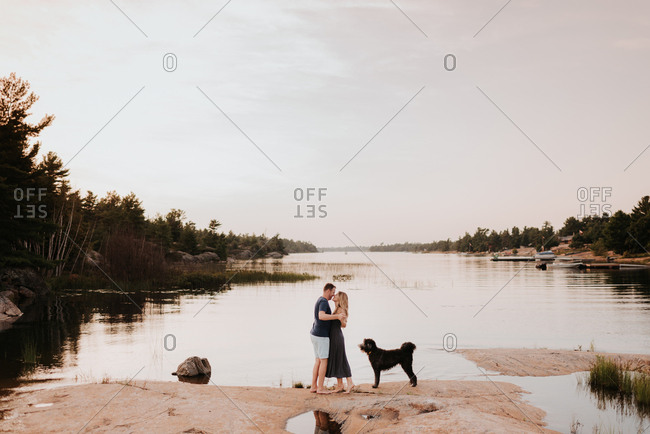 Couple enjoying view of river with pet dog, Algonquin Park, Canada