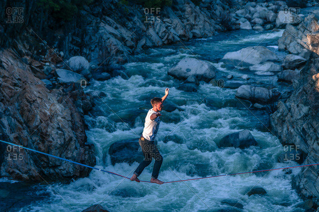 Man highlining above river, Truckee, California, USA