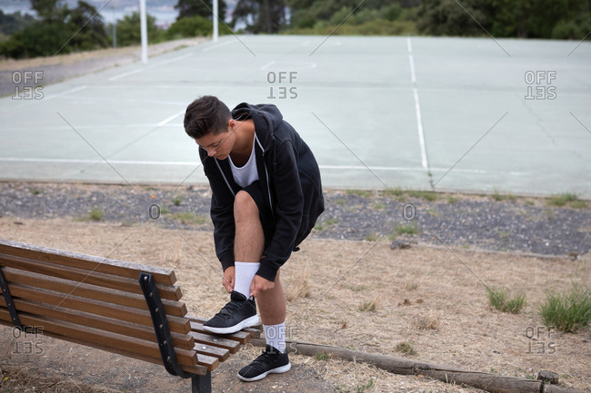 Male teenage basketball player fastening trainers by basketball court