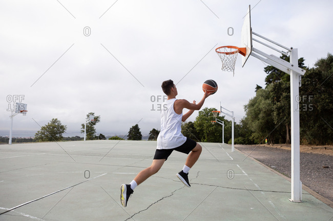 Male teenage basketball player jumping with ball toward basketball hoop