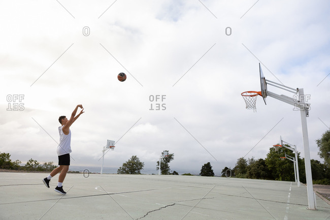 Male teenage basketball player throwing ball toward basketball hoop
