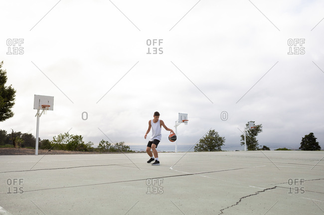 Male teenage basketball player practicing with ball on basketball court