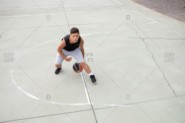 Male teenage basketball player practicing on basketball court, high angle view