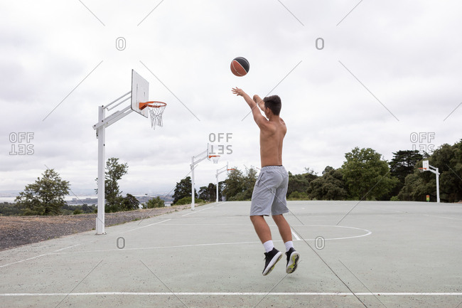 Male teenage basketball player jumping and throwing ball toward basketball hoop