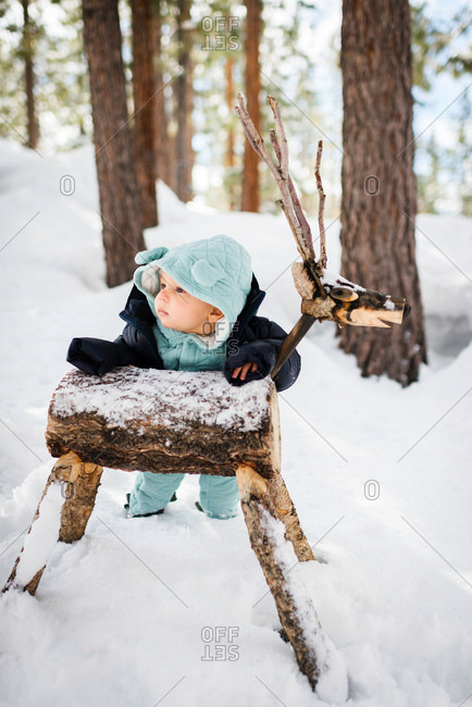 Baby boy ankle deep in forest snow leaning against wooden deer, South Lake Tahoe, California, USA
