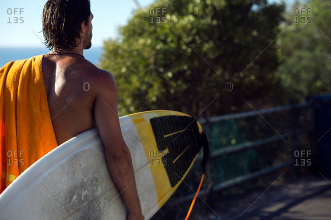 Mid adult male surfer carrying surfboard along beach walkway, rear view, Camps Bay Beach, Cape Town, South Africa