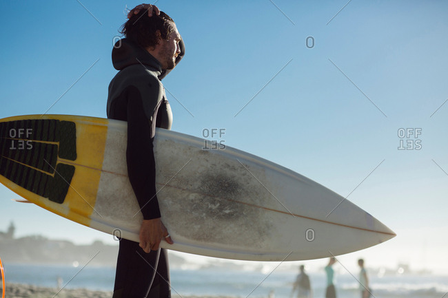 Mid adult male surfer in wet suit carrying surfboard on beach, Camps Bay Beach, Cape Town, South Africa