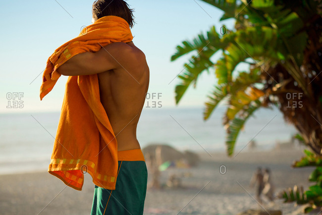 Mid adult male surfer drying off on beach, Camps Bay Beach, Cape Town, South Africa