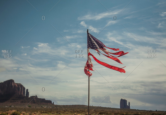 Tattered stars and stripes flag against Monument Valley backdrop, Utah, USA