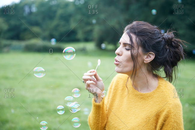 Woman playing with soap bubbles in field
