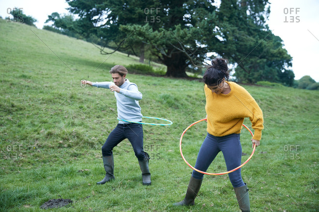 Couple hula hooping in field