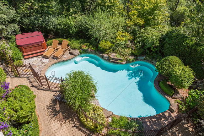 Outdoor swimming pool surrounded by wrought iron security fence and various shrubs and trees in luxury residential backyard, high angle view