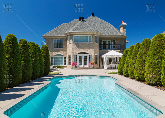 Outdoor swimming pool bordered by rows of cedar trees (Thuja occidentallis) at rear of luxurious house with beige stone