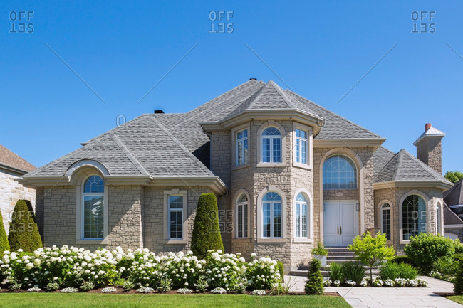 Facade of luxurious house in beige stone with front garden