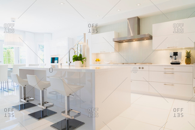 Modern kitchen with white Italian lacquered kitchen island and chrome barstools inside luxury residential home