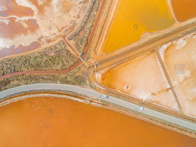 Aerial view of long road by colourful Saline Conti Vecchi, Cagliari, Sardinia