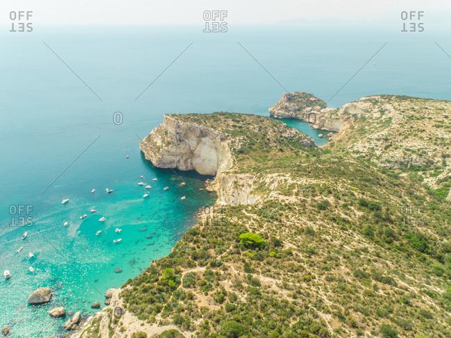 Aerial view of Sella del Diavolo rocky coast with yachts, Cagliari, Sardinia