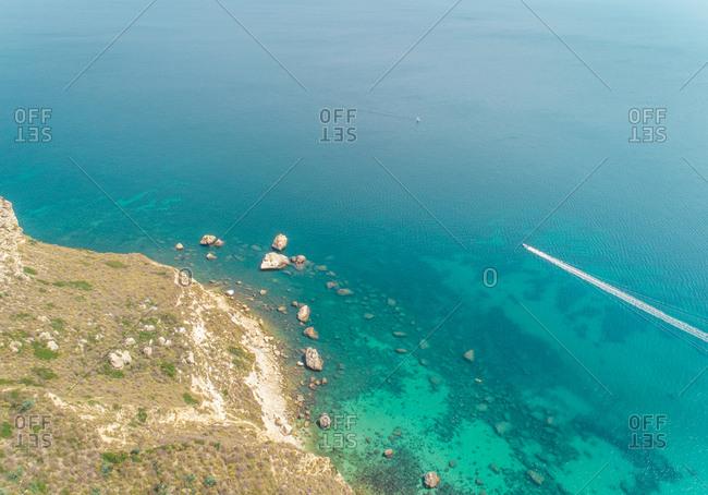 Aerial view of speed boat in sea by Sella del Diavolo coast, Cagliari, Sardinia