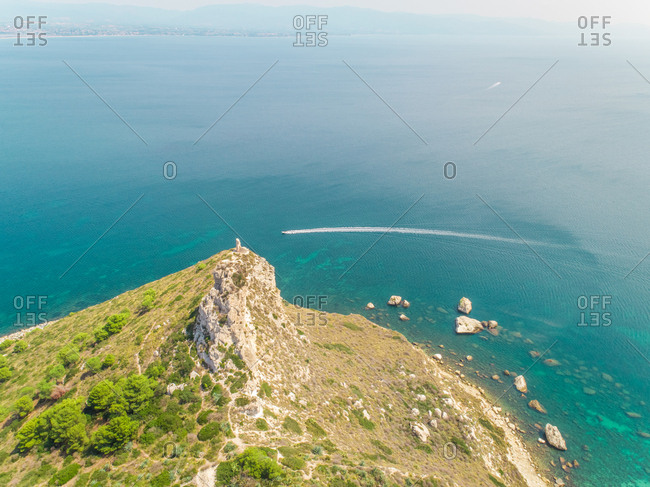 Aerial panoramic view of coastline, speed boat and rocks, Cagliari, Sardinia