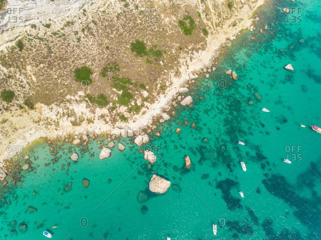 Aerial view of rocky coast and boats off Sella del Diavolo, Cagliari, Sardinia