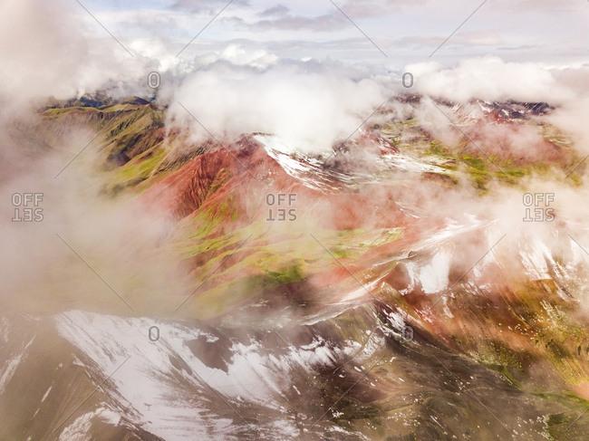 Aerial view of snowy, hazy Vinicunca, Rainbow Mountain, Peru