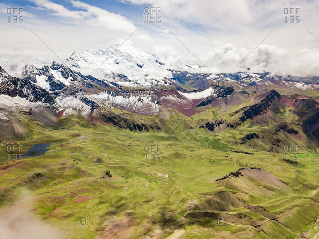 Aerial panoramic view green plateau and snowy peaks of  Vinicunca in clouds, Rainbow Mountain, Peru