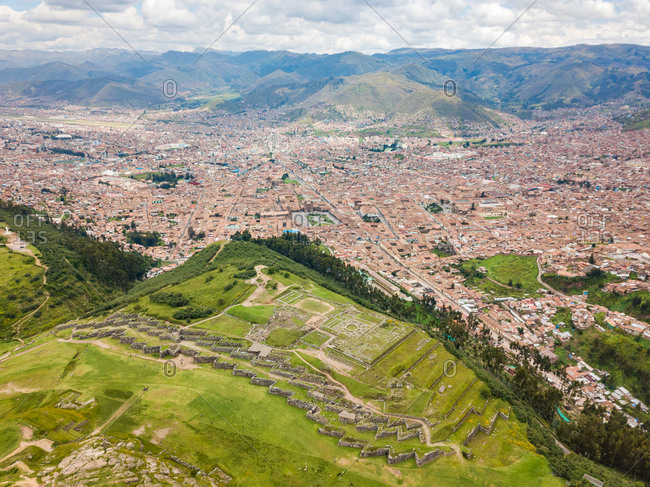 Aerial panoramic view of  Cuzco city with red rooftops and ruins, Peru