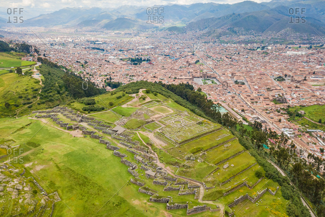 Aerial view of Cuzco city ruins, red rooftops and mountains, Peru
