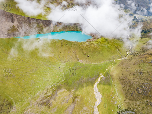 Aerial view of cloudy  Humantay Lake green valleys and mountains, Peru
