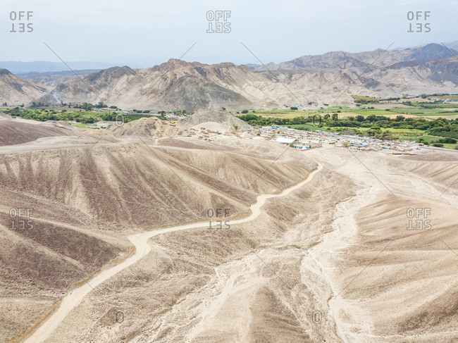 Aerial view of Nazca desert, town and mountains, Peru