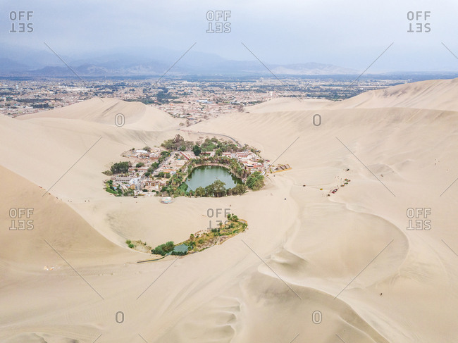 Aerial view of Huacachina desert oasis, city and mountains, Peru