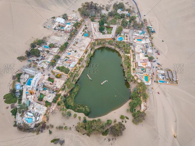 Aerial close up of Huacachina desert oasis resorts and swimming pools, Peru