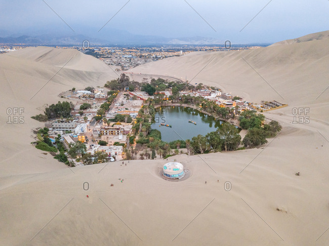 Peru - March 23, 2018: Aerial view of Huacachina desert oasis and city lights in background, Peru