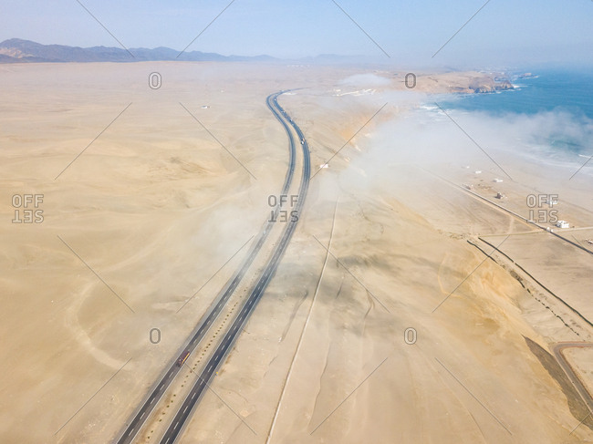Aerial view of long curved road in desert by coast, Asia district, Peru