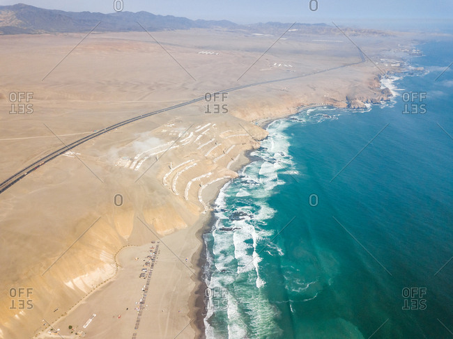 Aerial view of long road by coast and Sarapampa resort, Asia district, Peru