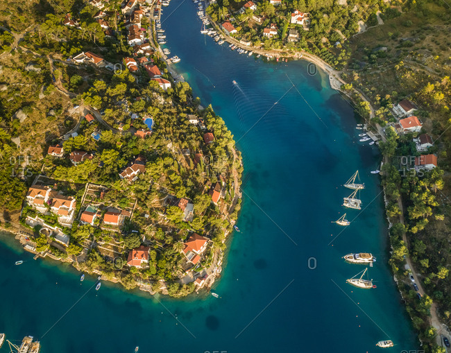 Aerial view of boats and houses with swimming pools in coastal town of  Sutivan, Brac island, Croatia