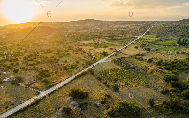 Aerial panoramic view of long road in Nerezisca dalmatian village with hills at sunset, Brac Island, Croatia