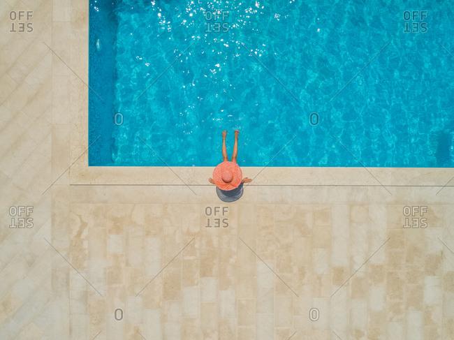 Aerial view of young girl in sunhat sitting by swimming pool, Sumartin, Brac island, Croatia