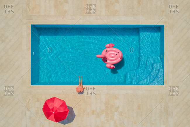 Aerial view of young girl in sunhat sitting by swimming pool with red parasol and inflatable flamingo, Sumartin, Brac island, Croatia